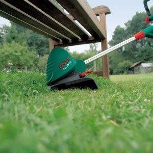 Rasentrimmer stutzt Grashalme unter Parkbank